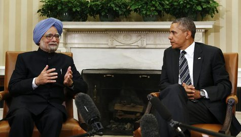 Indian Prime Minister Manmohan Singh (L) speaks as U.S. President Barack Obama looks on, during their meeting in the Oval Office of the Whit