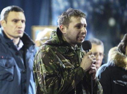 Anti-presidential protester Volodymyr Parasiuk addresses the crowd as opposition leader Vitaly Klitschko (L) looks on during a rally in Kiev