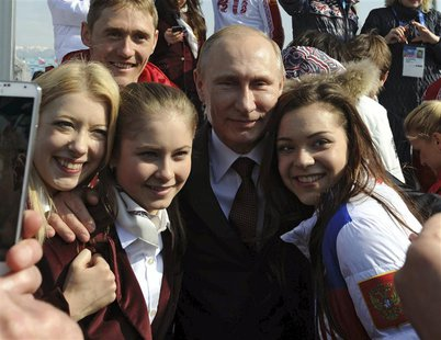 Russian President Vladimir Putin (C) and Russian Olympic medal winning athletes pose for a picture in Sochi February 24, 2014. REUTERS/Mikha
