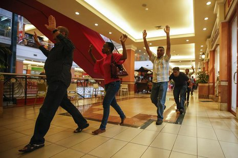 Shoppers and shop assistants raise their hands as they are escorted to safety while armed police hunt for gunmen who went on a shooting spre