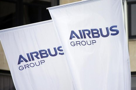 Flags with the new logo of aircraft manufacturer Airbus Group are seen on the entrance gate of the company's office building in Paris Januar