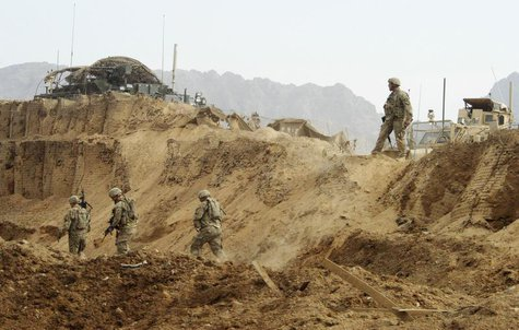 U.S. troops investigate the site of a suicide attack on a NATO base in Zhari, west of Kandahar province, January 20, 2014. REUTERS/Ahmad Nad