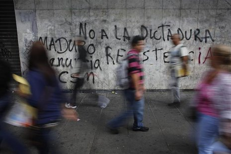 "Pedestrians walk past a wall covered with graffiti that reads, ""No to the dictatorship of Maduro"" at the district of Chacao in Caracas Febru"