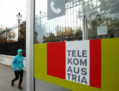 A jogger runs by a Telekom Austria phone booth in Vienna November 14, 2013. REUTERS/Heinz-Peter Bader