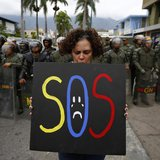 A demonstrator holds a placard as she stands in front of national guards during a protest near the Cuba's Embassy in Caracas February 25, 20