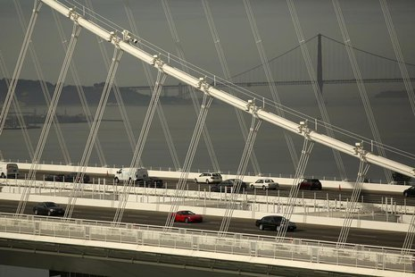 The Golden Gate Bridge is seen in the background as vehicles travel on the new east span of the San Francisco Oakland Bay Bridge in Oakland,
