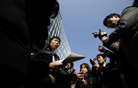 A Japanese investor (C) speaks to the media as he protests against Mt. Gox, in front of the building where the digital marketplace operator