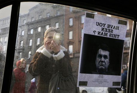 "A woman takes photos of a ""Wanted"" notice for fugitive Ukrainian President Victor Yanukovich, plastered on the window of a car used as a bar"