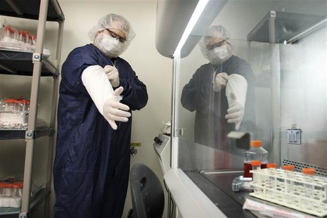 Derek Grice pulls additional sterilized covers on his arms in a Northwest Biotherapeutics laboratory in Memphis, Tennessee, February 21, 201