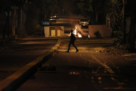 A woman walks past a burning barricade at Altamira Square in Caracas February 24, 2014. REUTERS/Carlos Garcia Rawllins