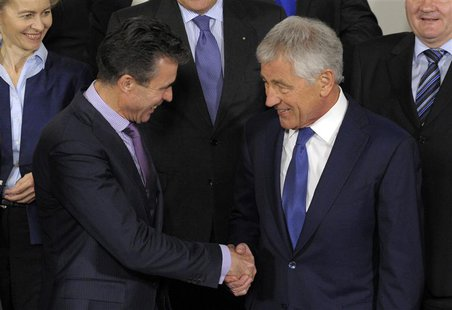U.S. Secretary of Defense Chuck Hagel (R) shakes hands with NATO Secretary-General Anders Fogh Rasmussen during a NATO defence ministers' me