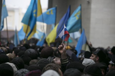 An ethnic Russian Ukrainian holds a Russian flag as Crimean Tatars rally near the Crimean parliament building in Simferopol February 26, 201