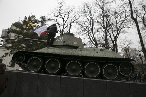 An ethnic Russian Ukrainian man holds the Crimea flag on top of an old Soviet tank during rallies near the Crimean parliament building in Si