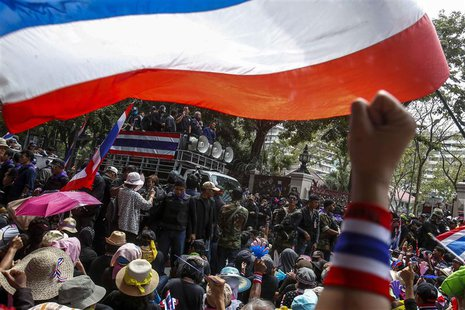 Anti-government protesters gather outside the Royal Thai Police headquarters as anti-government protest leader Suthep Thaugsuban (C, on vehi