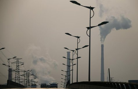 Smoke rises from chimneys of a steel plant next to a viaduct on a hazy day in Tangshan, Hebei province February 18, 2014. REUTERS/Petar Kuju