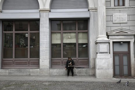 A woman reads a book outside a National Bank branch in Athens December 31, 2013. REUTERS/Yorgos Karahalis