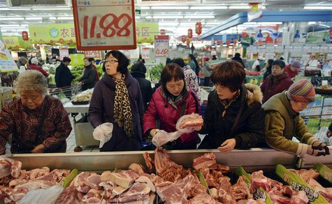 Customers select pork products under a price tag at a supermarket in Hangzhou, Zhejiang province January 9, 2014. REUTERS/China Daily