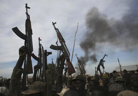 Rebel fighters hold up their rifles as they walk in front of a bushfire in a rebel controlled territory in Upper Nile State February 13, 201