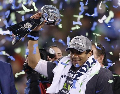 Seattle Seahawks quarterback Russell Wilson holds up the Vince Lombardi Trophy after the Seahawks defeated the Denver Broncos in the NFL Sup