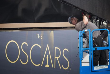 A man sets a digital display above the red carpet during preparations for the 86th Academy Awards in Hollywood, California February 26, 2014