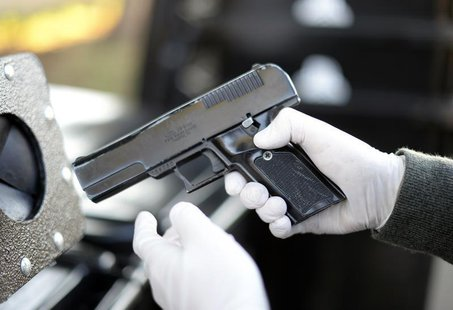A Los Angeles Police Department officer inspects a handgun in Los Angeles, California, December 14, 2013. REUTERS/Kevork Djansezian