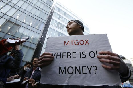 Kolin Burges, a self-styled cryptocurrency trader and former software engineer from London, holds a placard to protest against Mt. Gox, in f