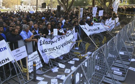 Demonstrators hold signs and banners outside Cyprus's parliament as they protest plans by the government to sell off state-owned enterprises