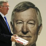 Former Manchester United manager Alex Ferguson poses with his new autobiography before a book signing at a supermarket in Manchester, northe
