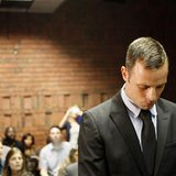 Oscar Pistorius stands in the dock during a break in court proceedings at the Pretoria Magistrates court, February 20, 2013. REUTERS/Siphiwe