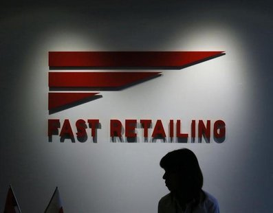 An employee of Fast Retailing Co, operator of the Uniqlo budget fashion chain, is silhouetted in front of its logo at its headquarters in To