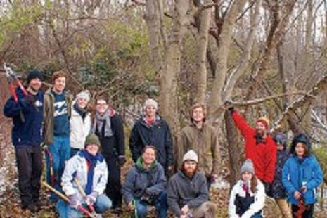 Stephan Keto with students, alumni and volunteers in front of the large dwarf hackberry tree.