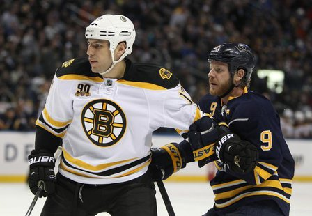 Feb 26, 2014; Buffalo, NY, USA; Boston Bruins left wing Milan Lucic (17) and Buffalo Sabres center Steve Ott (9) battle for position during