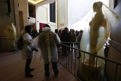 Tourists wearing rain gear stand next to Oscar statues covered with plastic during preparations for the 86th Academy Awards at the Dolby The
