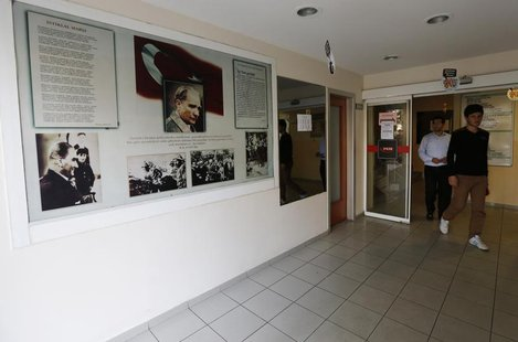 Students walk past photographs of modern Turkey's secular founder Mustafa Kemal Ataturk hanging on a wall at the entrance of FEM University