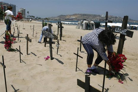 Anti-government protesters place crucifixes with names of victims of violence as a form of protest at the beach in Puerto La Cruz March 1, 2