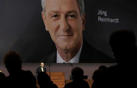 Designated successor Joerg Reinhardt is seen on a huge TV screen as outgoing Chairman of Swiss drug maker Novartis Daniel Vasella addresses