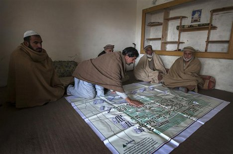 Local elders point to their fruit orchards on a map showing lands, taken over by the army for a base, in the town of Khwazakhela in the nort