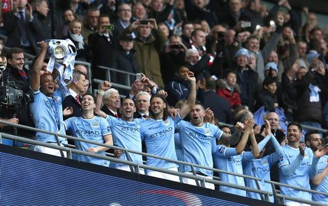 Manchester City captain Vincent Kompany holds aloft the trophy after defeating Sunderland to win the English League Cup final soccer match a