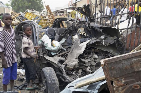 Two boys stand near the charred chassis of a vehicle after a bomb attack near a busy market area in Ajilari-Gomari near the city's airport,