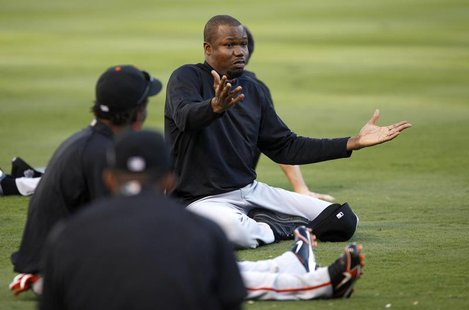 San Francisco Giants Guillermo Mota talks with teammates while he stretches during workouts ahead of Game 3 of Major League Baseball's World
