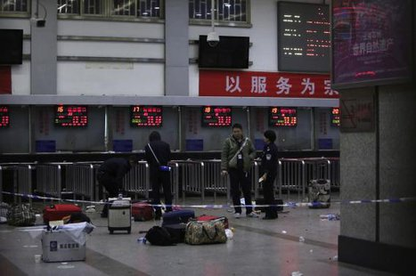 Police stand near luggages left at the ticket office after a group of armed men attacked people at Kunming railway station, Yunnan province, March 2, 2014. Credit: REUTERS/Stringer