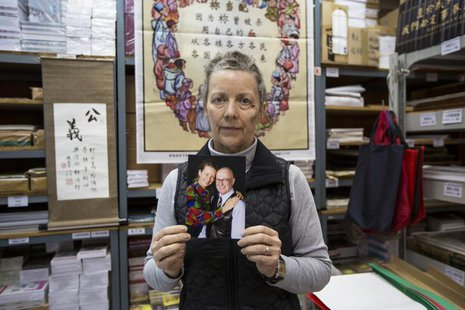 Karen Short, wife of Australian missionary John Short, poses with a photo of her husband inside the Christian Book Room in Hong Kong Februar