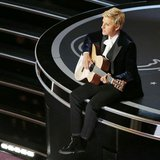 Host Ellen Degeneres plays a guitar at the 86th Academy Awards in Hollywood, California March 2, 2014. REUTERS/Lucy Nicholson
