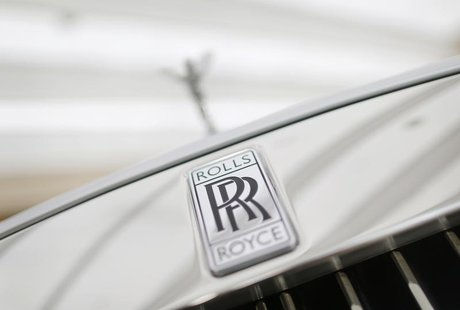 A Rolls-Royce mascot known as 'Spirit of Ecstasy' stands above the brand's logo on the front of a Rolls-Royce Ghost in a showroom in Singapo