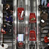 Shoppers ride an escalator at a Target Store in Chicago, November 25, 2011. REUTERS/John Gress