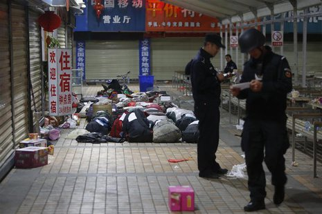 Policemen check unclaimed luggage at a square outside the Kunming railway station after a knife attack, in Kunming, Yunnan province March 2,