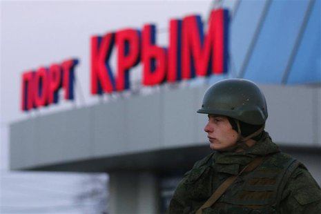 An armed man, believed to be a Russian soldier, stands outside the civilian port in the Crimean town of Kerch March 3, 2014. REUTERS/Thomas