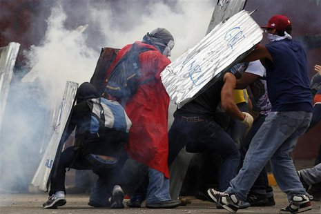 Anti-government protesters shield themselves from tear gas during a rally in Caracas March 2, 2014. REUTERS/Jorge Silva