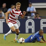 Stuart Holden (L) of the U.S. moves the ball away from Honduras' Alexander Lopez during their CONCACAF Gold Cup soccer match in Arlington, T