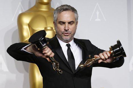 "Alfonso Cuaron poses with the awards for best director and best film editing for ""Gravity"" at the 86th Academy Awards in Hollywood, Californ"